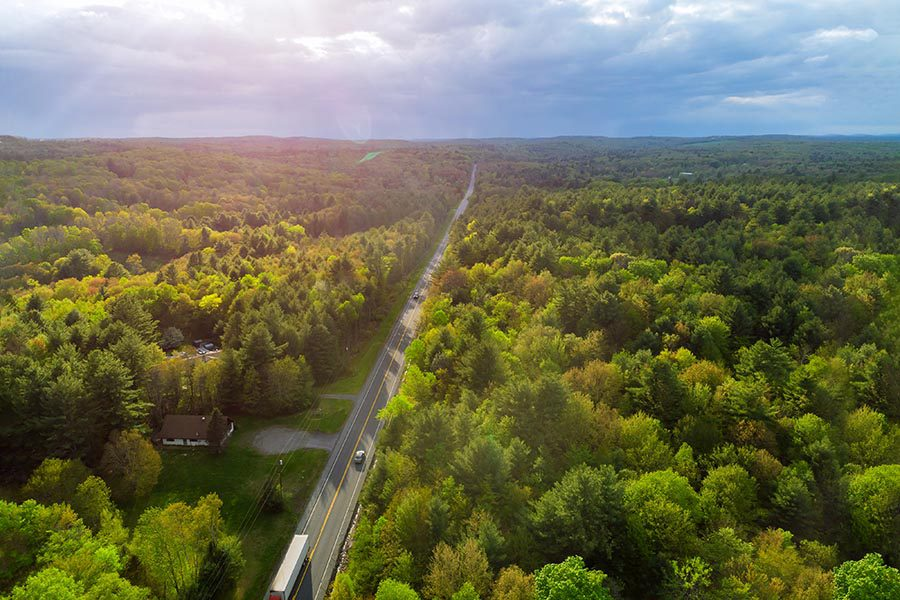 Allentown, PA Insurance - Long Highway Cuts Through a Vast Forest of Green Trees Stretching Into the Distance Where Low Hills and Valleys Sit Under a Cloudy Sky
