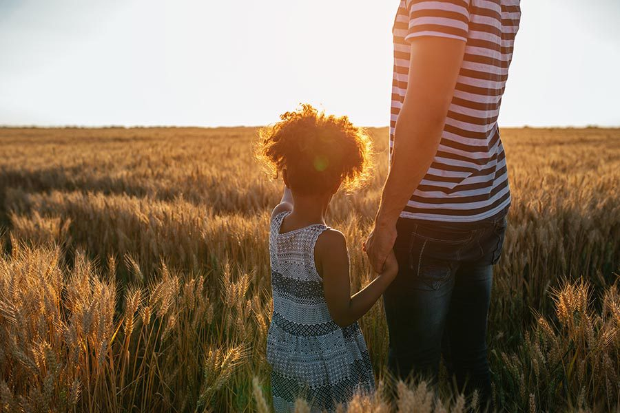 Personal Insurance - Young Girl in Sundress Holds Her Father's Hand as They Gaze Over a Field of Golden Wheat