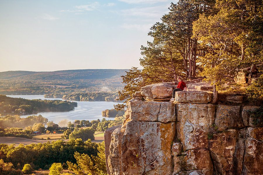 Contact - Aerial View of Trees, River and Rock Ledge in Wisconsin With a Person Sitting Close to Edge of a Cliff at Dusk