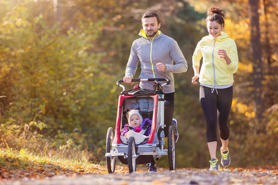 Employee Benefits - Parents With Small Child Riding in Stroller While Jogging Through Nature on a Fall Morning