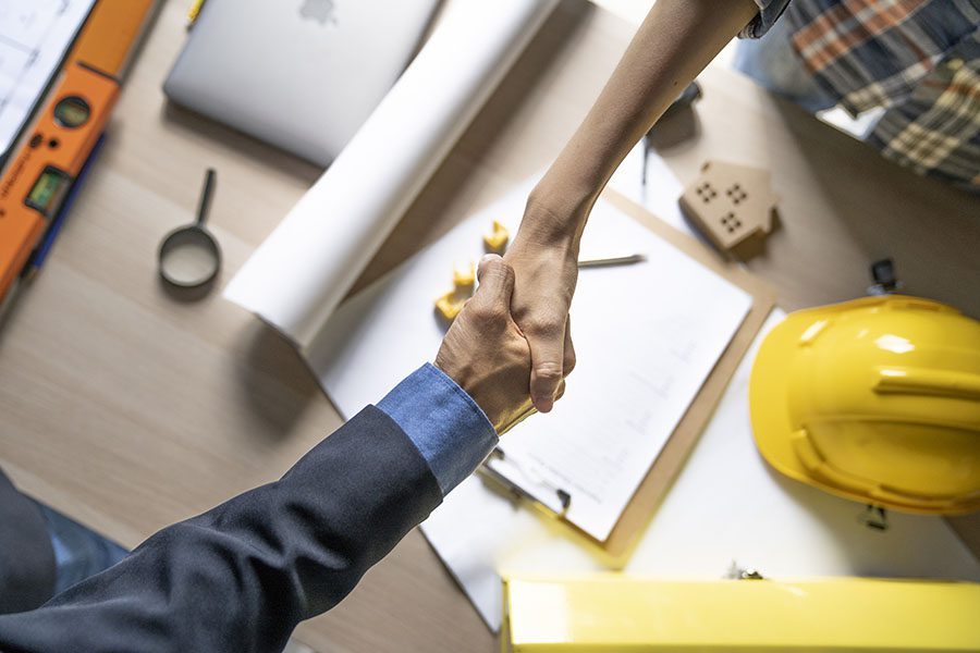 Specialized Business Insurance - Contractor and Businessman Shaking Hands Across Wooden Table with New Construction Blueprints