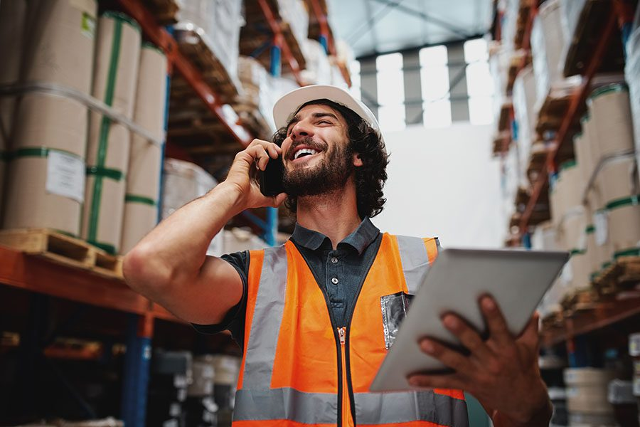 Client Center - Factory Worker Using a Phone and Tablet at the Warehouse