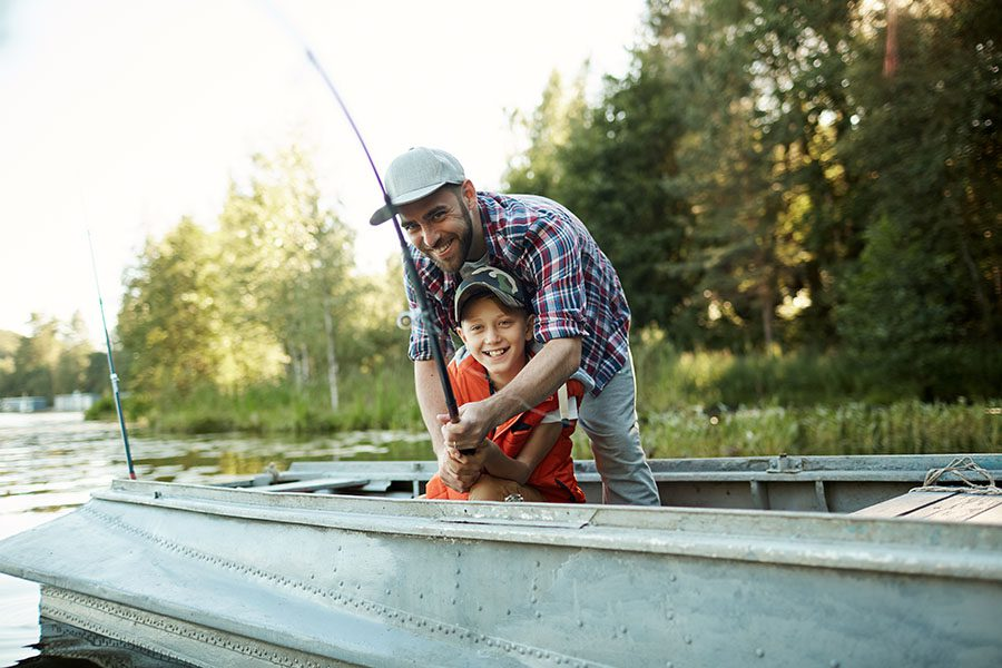 Personal Insurance - Happy Father and Son Fishing on a Boat in the Lake