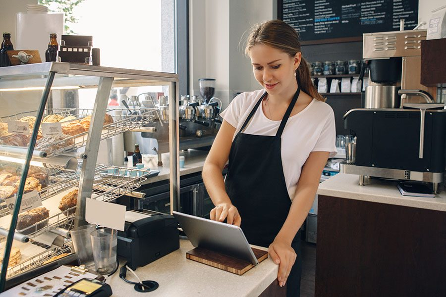 Business Insurance - Portrait of a Small Business Coffee Shop Owner Using a Tablet to Process Payments
