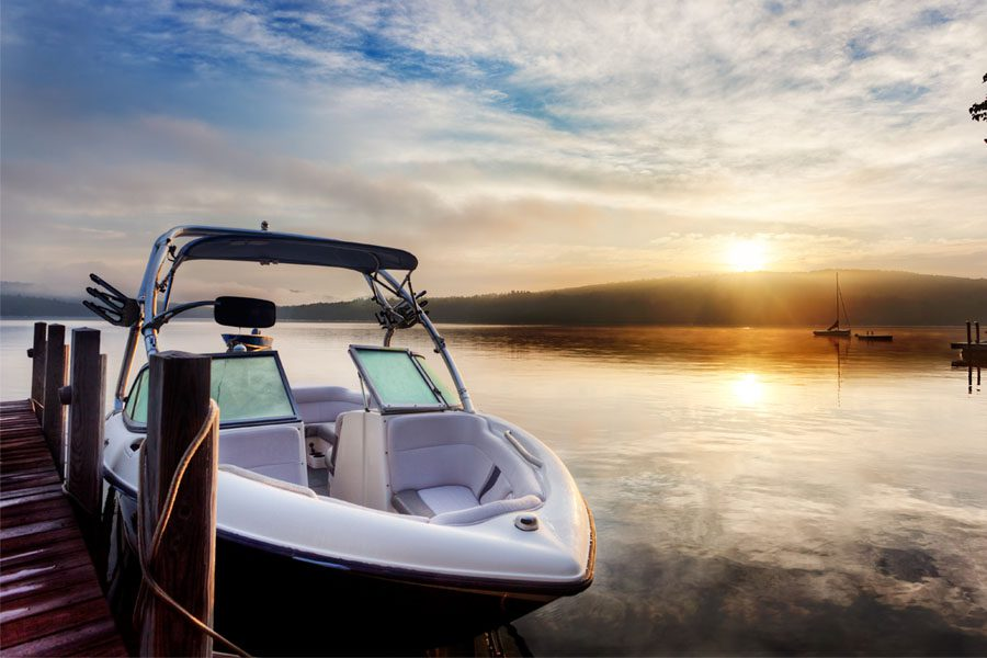 Watercraft Insurance - View of a Boat Parked at the Dock on a Calm Lake at Sunset
