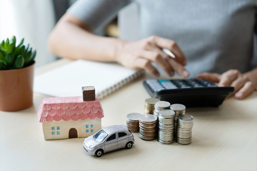 Bundling Home and Auto Insurance - Picture of a Woman's Hands with a House and Car on the Desk