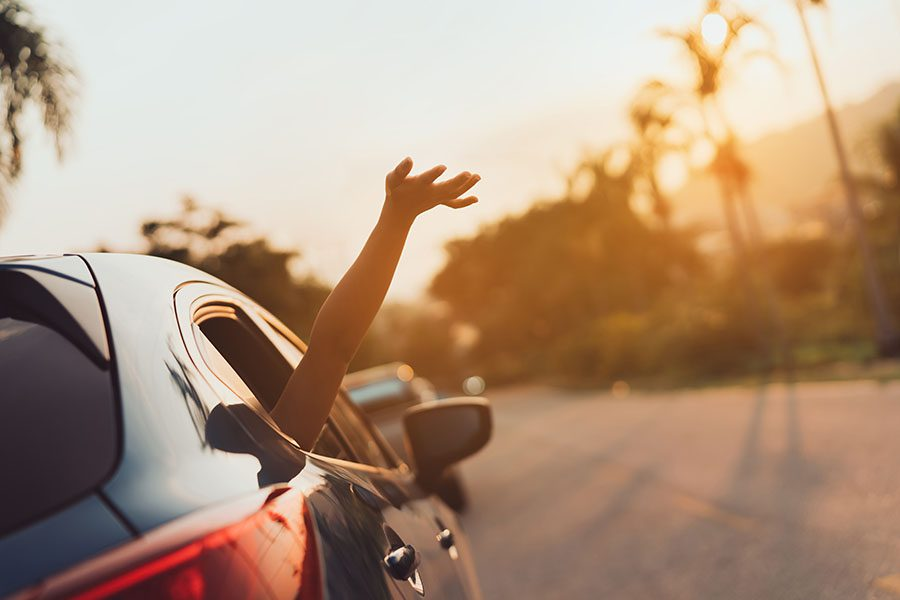 Insurance Quote - View of Woman Sticking Her Hand Out of Car Window at Sunset During Road Trip