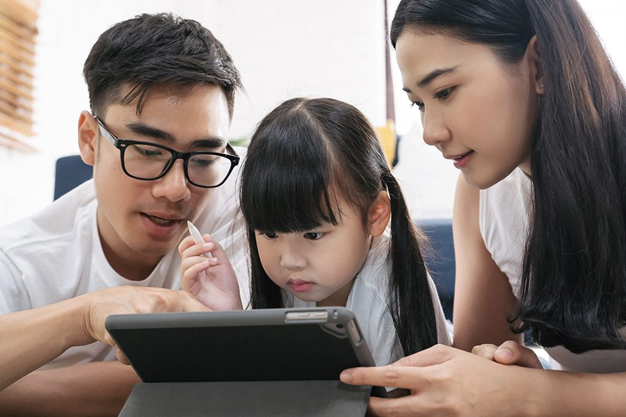 Blog - Closeup of Family Spending Time Together in Living Room and Using a Tablet
