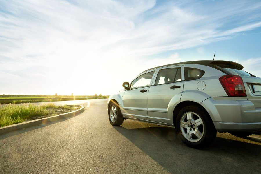 Auto Insurance - View of a Modern Four Door Car Driving on Empty Road at Sunset