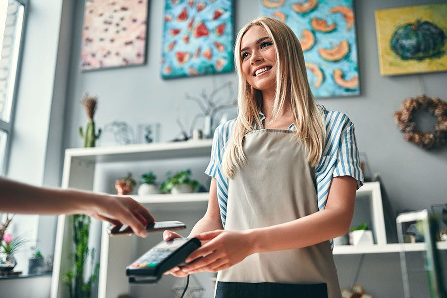 Business Insurance - Cheerful Small Business Owner Receiving Payment from a Customer
