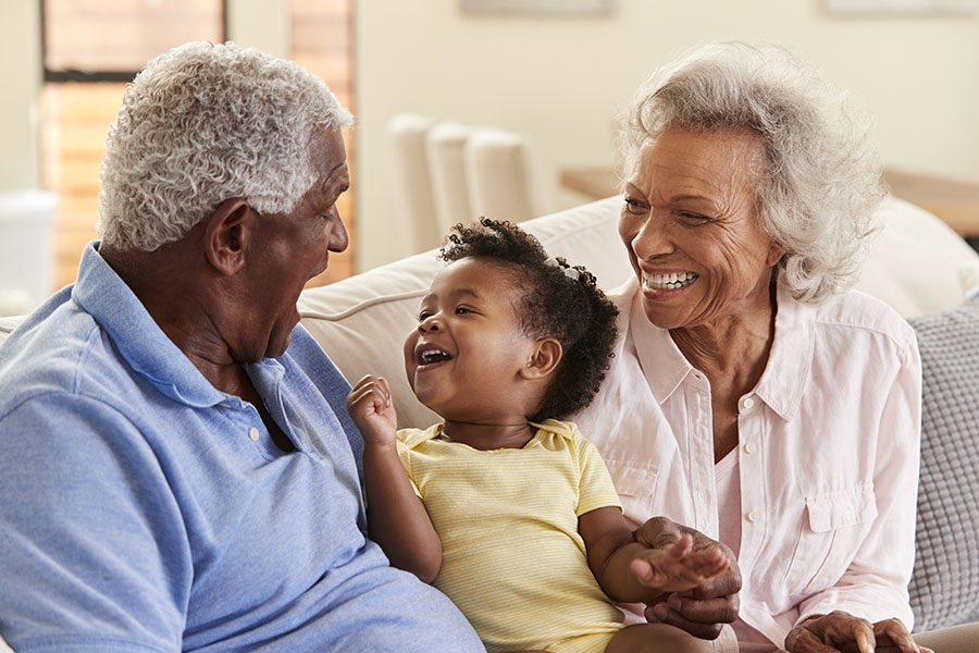 Health Insurance - Happy Grandparents Sitting on the Sofa Playing with Their Grandaughter