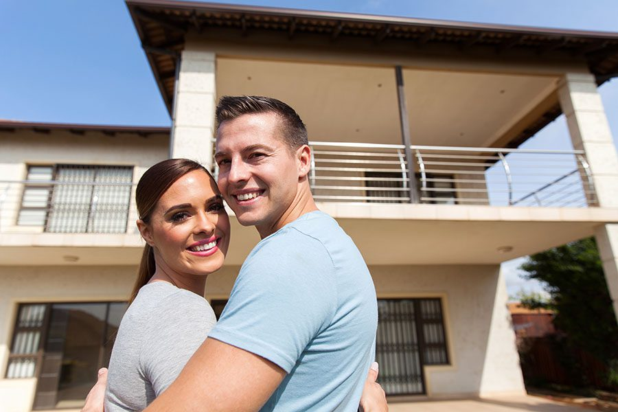 Personal Insurance - View of Happy Young Couple Standing in Front of Their New Home
