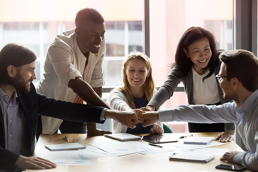 Employee Benefits - Group of Happy Employees Sitting in the Office Putting Their Fists Together in Celebration