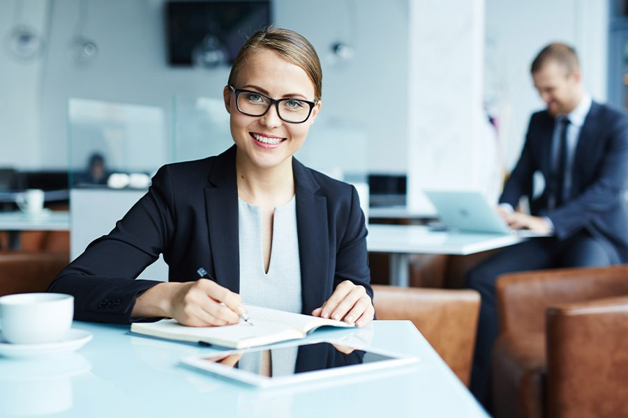 Business Insurance - Successful Businesswoman Sitting at Her Desk with Colleague in the Background