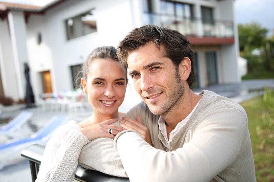 Personal Insurance - Closeup of Couple Standing Outside in Front of New Home