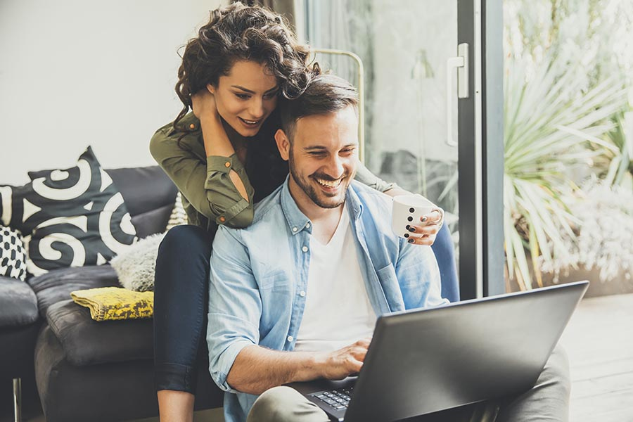 Blog - Smiling Man Uses His Laptop on the Floor, While His Wife Sits Behind Him on a Sofa Leaning on His Shoulders and Reading Along, a Coffee Cup in Her Hand