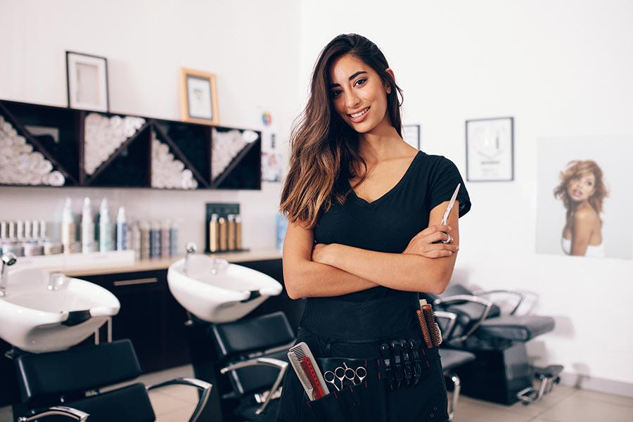 Specialized Business Insurance - Hair Salon Owner Poses in Front of the Salon Sinks and Leather Chairs, Scissors in Hand and More Tools Tucked in Her Apron