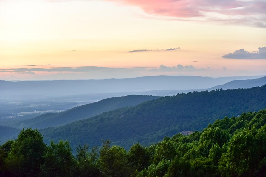 Tennessee Insurance - Sweeping View of the Blue Ridge Mountains, Mist Settling Over a Small Town in the Valley, a Pink Sunset Overhead and Green Trees in the Foreground