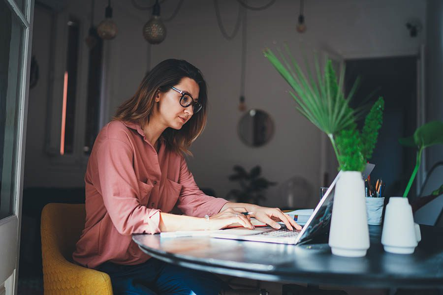 Client Center - Young Woman in Business Casual Clothing and Glasses Uses Her Laptop at a Table by a Window in Her Modern Office Surrounded by Plants