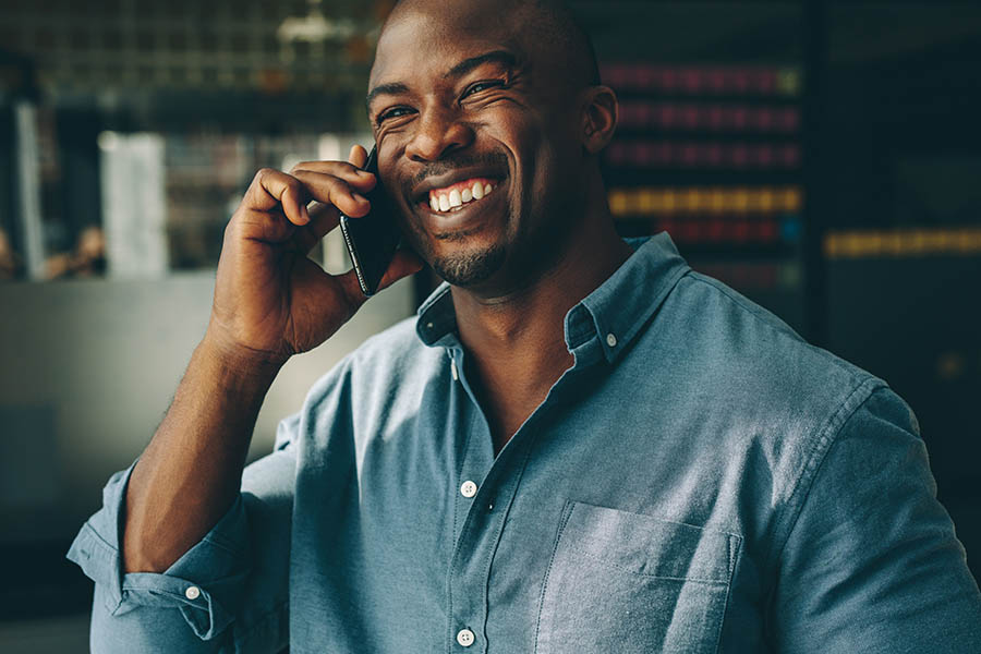 Contact Us - Man Smiling Broadly in a Button-Down Denim Shirt Makes a Phone Call in His Dark Modern Office