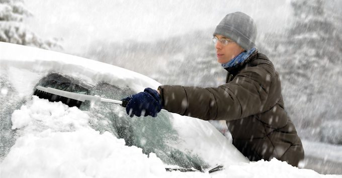 Man wiping his car of snow