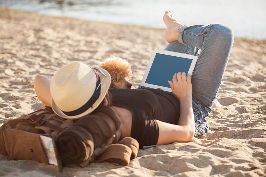 Client Center - Woman Traveler with Her Dog Holding Tablet While Relaxing Outdoors During on the Beach