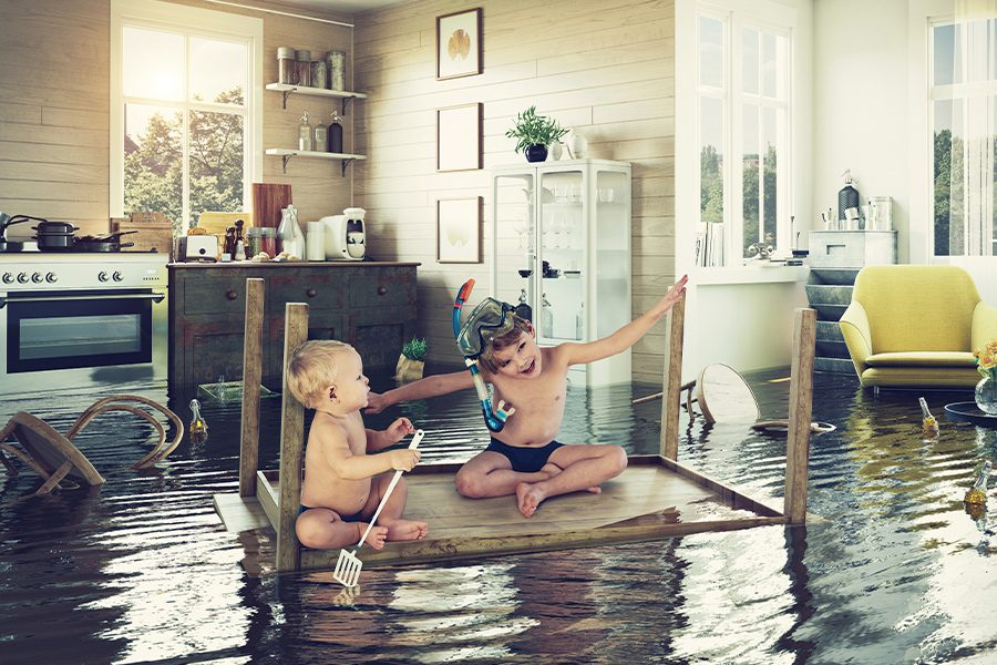 Flood Insurance - Children in the Center of a Flooded Living Room in Bathing Suits and Snorkel Gear
