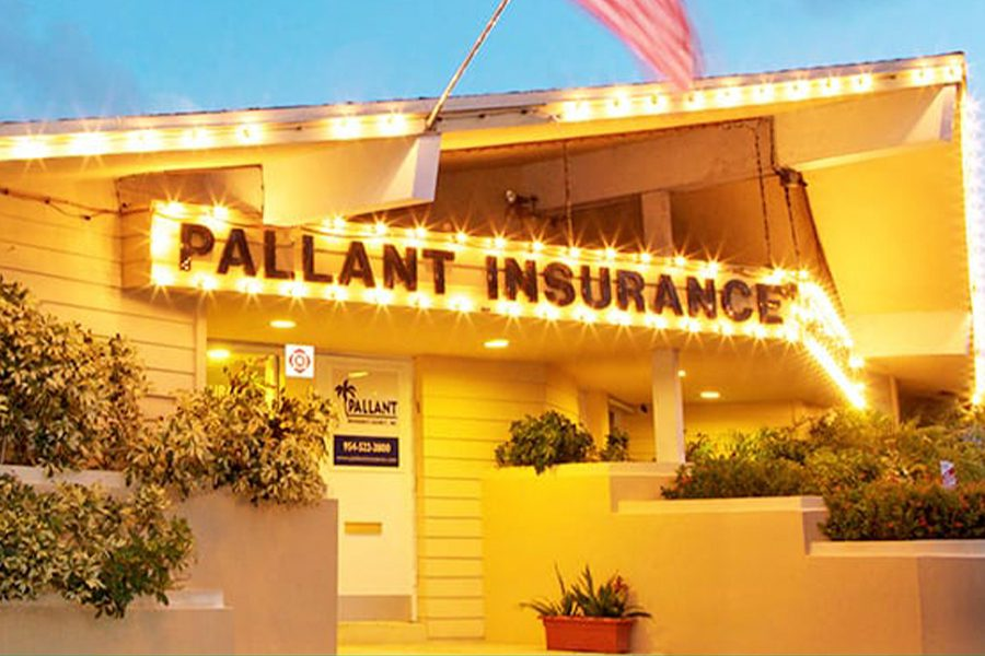 Fort Lauderdale, FL - Closeup View of Pallant Insurance Agency Office Building at Night with String Lights and American Flag