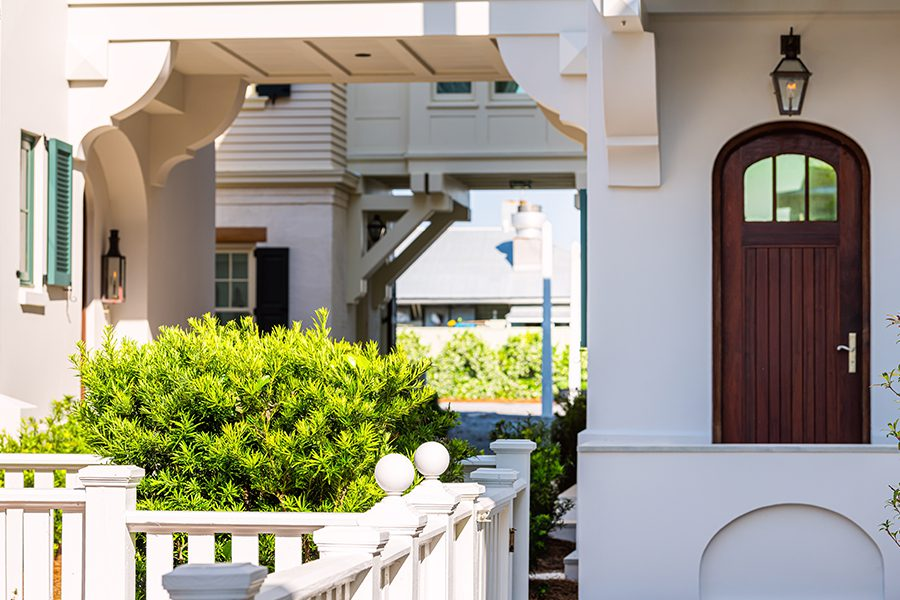 Home Insurance - Seaside White Beach Home with Wooden Architecture Path Way with Green Landscaping on a Sunny Day