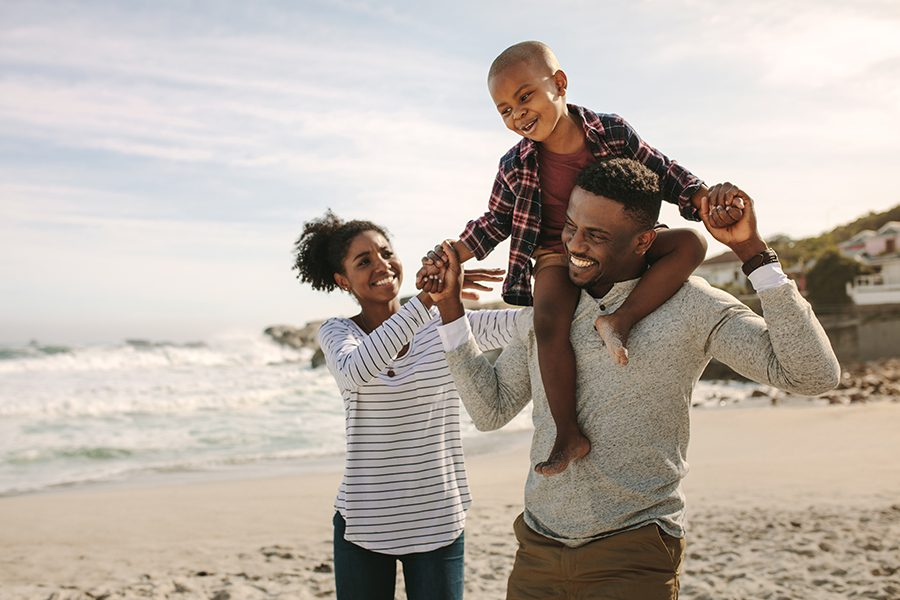 Personal Insurance - Parents Carrying Son on Shoulders on Beach Vacation in Fort Lauderdale, Florida