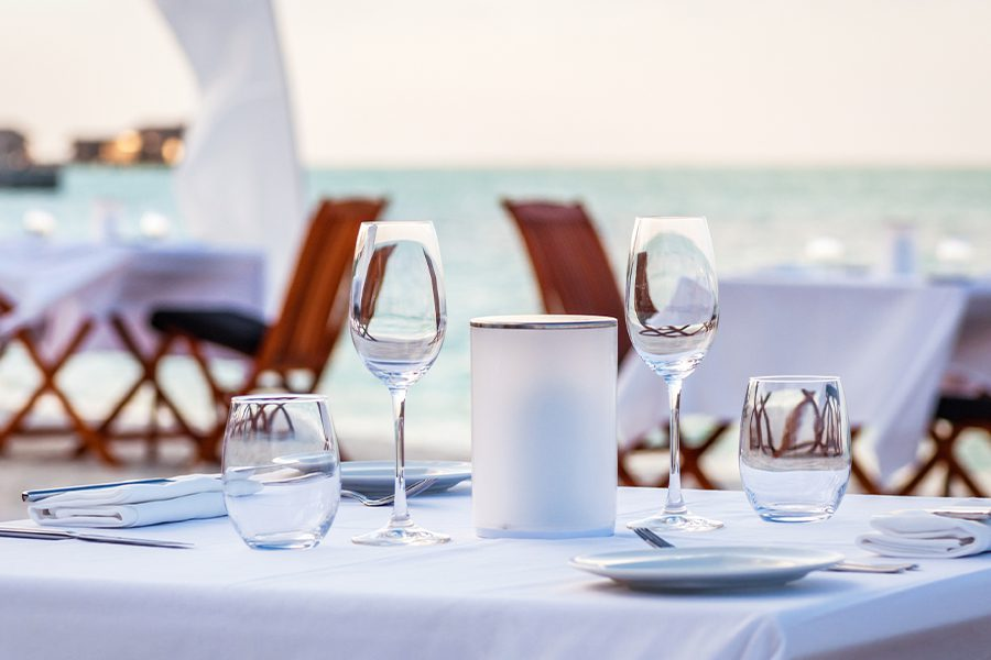 Specialized Business Insurance - Fine Dining Restaurant Table Set Up for Dinner on the Beach at Dusk