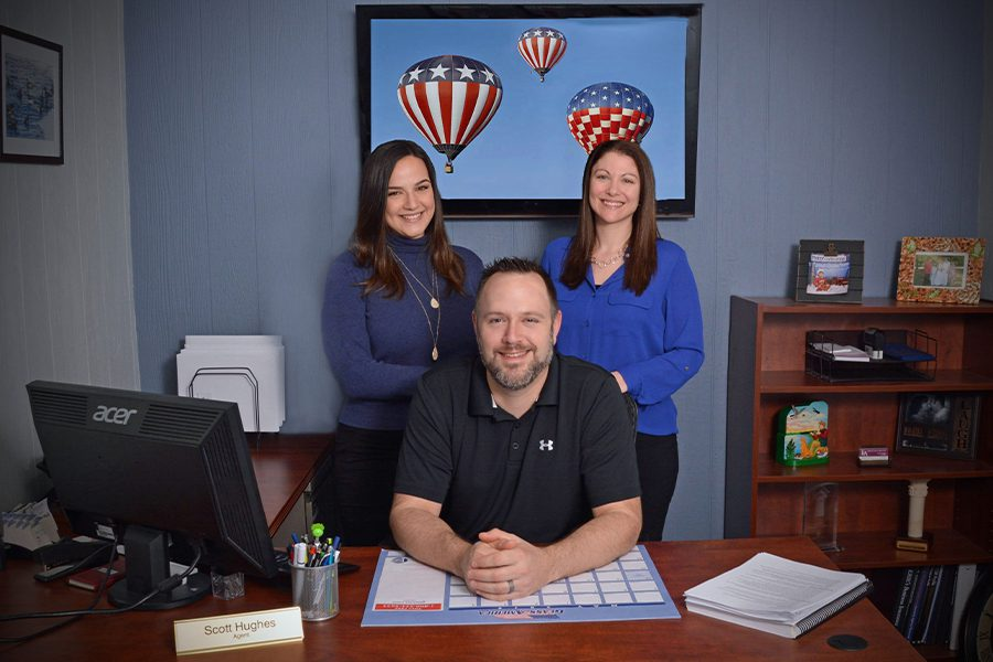 About Our Agency - The Leighton Insurance Agency Team Sitting and Standing Behind the Desk of their Office With Lots a Patriotic Theme
