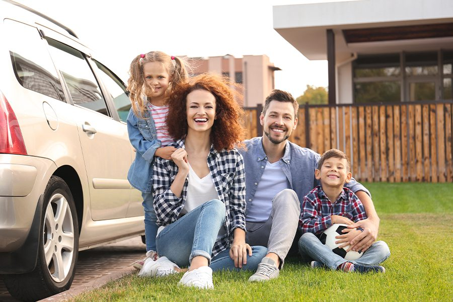 Blog - Young Family with their Children Sitting Next to their Car in Front of Their Home Outside on a Sunny Afternoon