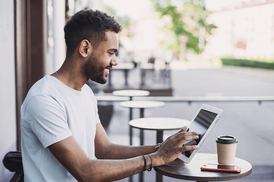 Client Center - Smiling Young Man Enjoying Coffee Using a Digital Tablet in New York
