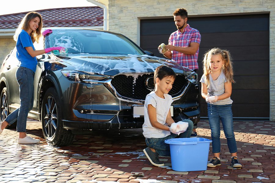 Personal Insurance - Happy Family Washing Car in the Backyard Behind their Home on a Sunny Day