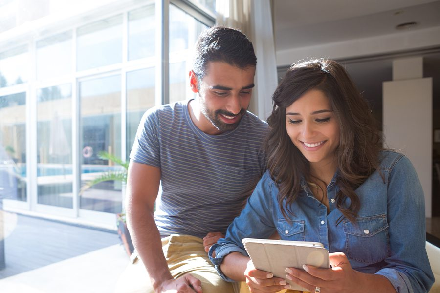 Client Center - Young Couple Using a Tablet Together by the Window with Sun and Lens Flare