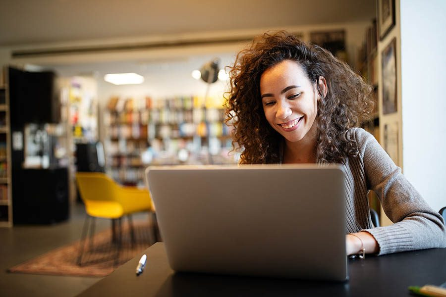 Client Center - Young Woman With Curly Hair and Tan Sweater Smiles as She Uses Her Laptop in a Colorful Coffee Shop