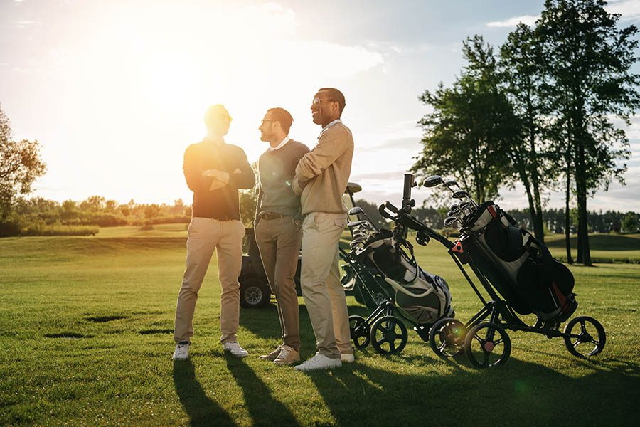Medinah, IL Insurance - Three Business Associates Pause on the Golf Course at Sunset With Trees and Golf Bags Behind Them