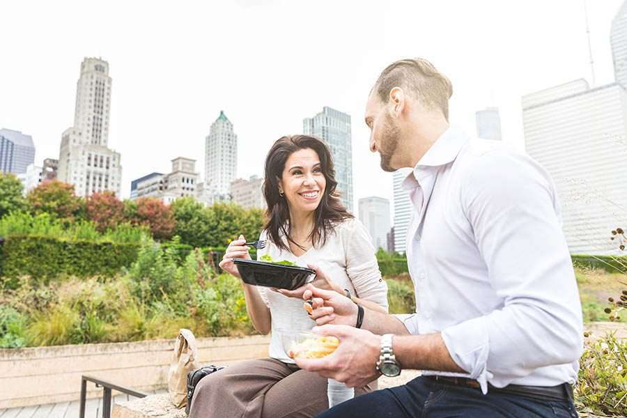 Level Funded Health Insurance - Man and Woman in Business Attire Sit on a Park Bench Enjoying Healthy Lunches With Foliage and Chicago Skyline Behind Them on an Overcast Day