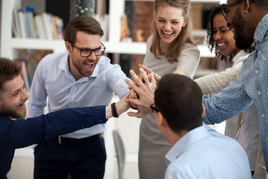 About Our Agency - Excited Motivated Business Team Giving Each Other High Five in the Office