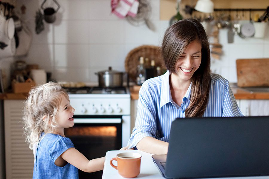 Blog - Happy Mother and Daughter Smiling While Mother Blogs on Her Laptop in the Kitchen