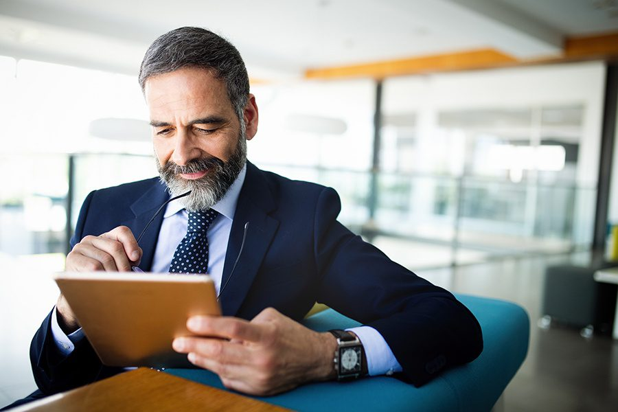 Client Center - Businessman Using a Tablet Device in the Office