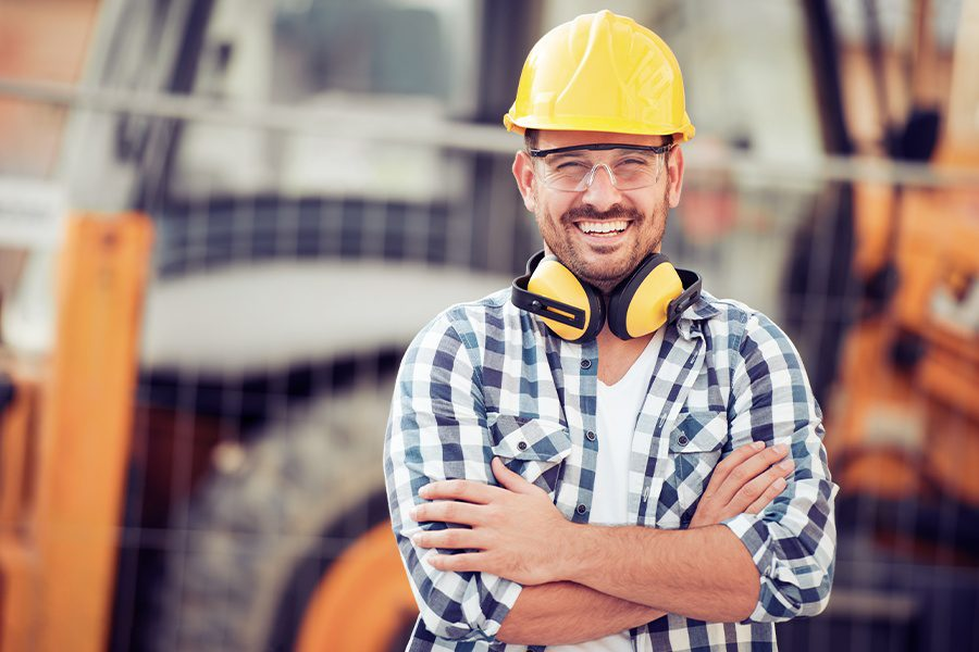 Business Insurance - Smiling Construction Worker at Site with Equipment Blurred in the Background