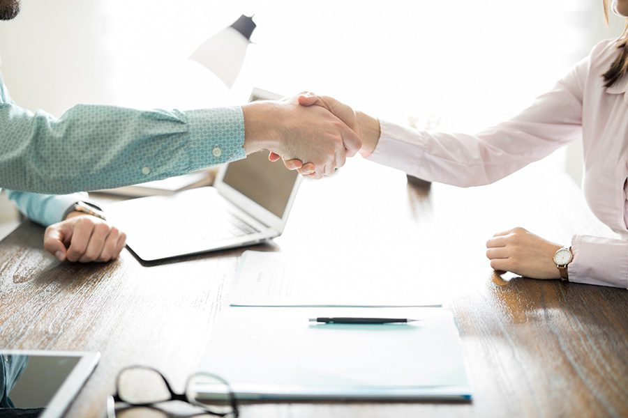 About Our Agency - Handshake of a Business Man and Woman Conducting an Insurance Quote Agreement on a Bright Sunny Day in the Office