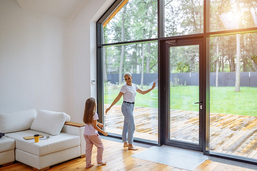 Personal Insurance - Mother and Daughter Standing Near a Panoramic Window Together Spending Time at Their New Modern Family Home