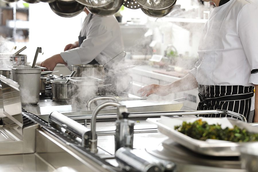 Specialized Business Insurance - Closeup of Chefs in a Hotel Restaurant Kitchen Cooking with Cooking Equipment Blurred in the Foreground