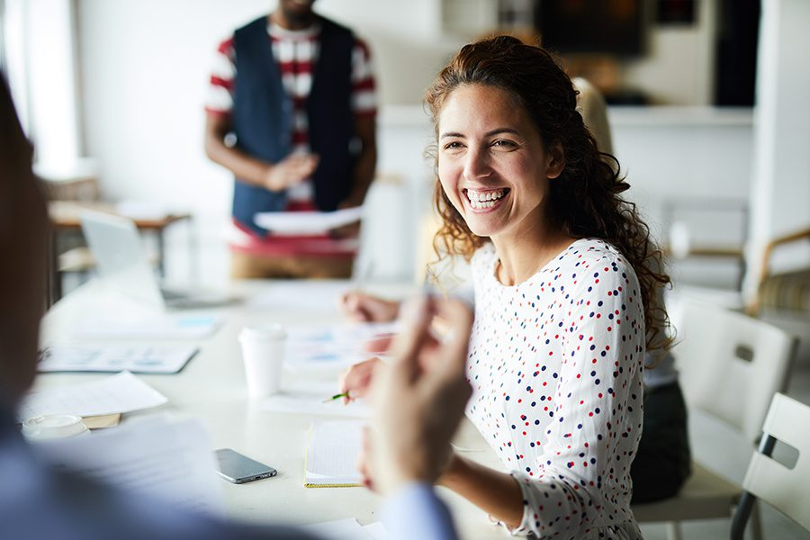 About Our Agency - Happy Businesswoman Sitting at Office Conference Table and Communicating with Her Colleagues During a Meeting