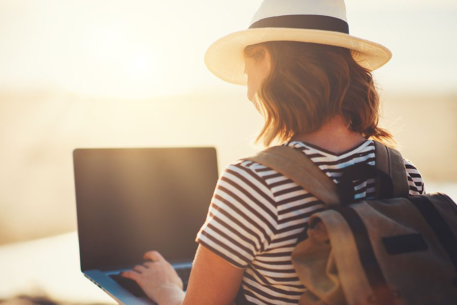 FAQs - Young Woman Using Her Laptop at the Beach On Sunny Day