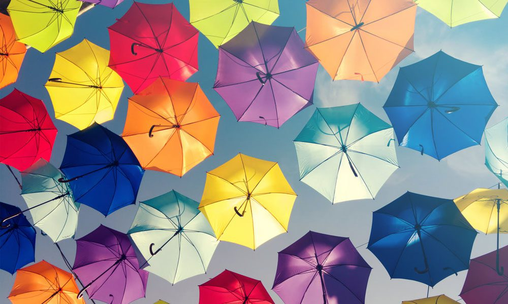 Blog - Colorful Umbrellas Floating Under a Clear Sky on a Sunny Day