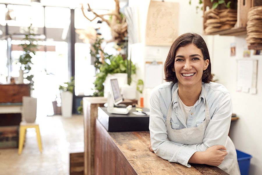 Business Insurance - Portrait Of Smiling Female Associate Standing Behind Sales Desk Of Florist Store